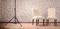 Interior of studio with chairs and brick wall two wooden white lightstand Stock Image