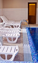 Interior of swimming pool with deck chair Stock Photography