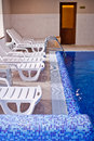 Interior of swimming pool with deck chair Stock Photo