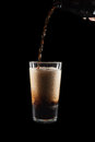 International Beer Day. Stout ale being poured in to a pint glass. Against black background. Royalty Free Stock Photo