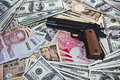 International crime a gun placed on iternational currencies portrays linkage of Stock Images