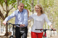 International family of active pensioners smiling couple with bikes outdoor Royalty Free Stock Image