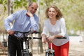 International family of active pensioners smiling couple with bikes outdoor in sunny day Stock Images