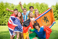 International sports friens group of fans each dressed in the color of their country and carrying the their nation s flag Stock Photo