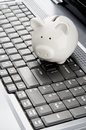 Internet banking piggy bank over a laptop keyboard as a symbol of technology and information cost or Royalty Free Stock Images