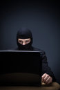 Internet criminal or hacker dressed in black clothing and a balaclava sitting behind a laptop computer stealing personal Royalty Free Stock Photos
