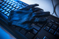 Internet security and fraude black glove on black computer keyboard in blue light Stock Images