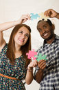 Interracial charming couple wearing casual clothes holding up large puzzle pieces and interacting happily, white studio Royalty Free Stock Photo