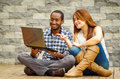 Interracial charming couple wearing casual clothes sitting down on wooden surface lookin at laptop together, in front of Royalty Free Stock Photo