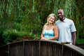 Interracial couple at a park beautiful portrait in summer standing on bridge Royalty Free Stock Photo