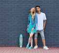 Interracial young couple in love outdoor whis skateboard. Stunning sensual outdoor portrait of young stylish fashion couple posing Royalty Free Stock Photo
