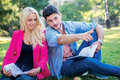 Interrupt academically couple of students sitting on the grass and smiling at camera while teaching lessons a break near Royalty Free Stock Images