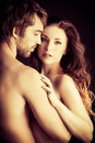 Intimacy beautiful passionate naked couple in love over black background Stock Image