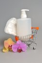Intimate gel dispenser pump plastic bottle sanitary towel in pushcart with orchid flowers and on gray Stock Image