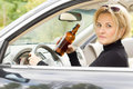 Intoxicated woman driver looking out of her side window with a serious expression as she drives by holding a bottle of booze in Royalty Free Stock Image