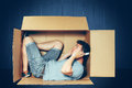 Introvert concept. The man sitting inside box and working with laptop Royalty Free Stock Photo