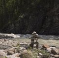 Inukshuk rock formation on river bank Stock Images