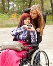 Invalid girl on the wheelchair with helper Stock Images