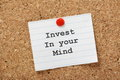 Invest in your mind typed onto a lined paper note pinned to a cork notice board we improve our minds via education and learning Stock Photos