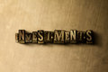INVESTMENTS - close-up of grungy vintage typeset word on metal backdrop