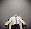 Invisible man in formal wear sitting on armchair against grey background Stock Image