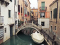 The invisible side of venice italy – march narrow venetian canal with small bridge and anchored boat young woman hotel servant Stock Photos