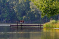 Inviting Park Bench on Pier Over Rustic Lake Royalty Free Stock Photo