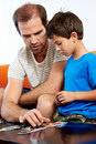 Involved dad father helps son with puzzle Stock Photography