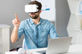 Involved serious man sitting at the table in work pleasant concentrated and working while using virtual reality device Stock Images