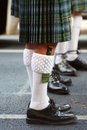 Irish costume close up shot of the legs of a traditional bagpipe player wearing black shoes intricate white woollen socks and Royalty Free Stock Images