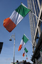 Irish flags in a row of attached to the building fluttering wind against blue sky Royalty Free Stock Photos