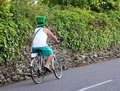 An irishman in a green st patrick s day hat gentleman paddy and shorts cycles up the road knightstown ireland Royalty Free Stock Image