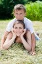 Irmão novo e irmã mais idosa ou mãe filho que sorriem junto no feno seco no dia de verão Imagem de Stock