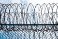 Iron Barbed wire in the blue sky with clouds Royalty Free Stock Photo