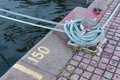 Iron berth holding white boat lines near sea and signs Royalty Free Stock Photography