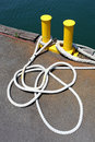 Iron bollard and rope painted in yellow at the harbor Stock Image