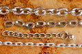 Iron chains collection different connection links. Brown rusty metal background. Macro view shallow depth field.