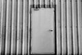 Iron door on corrugated metal sheet, black and white photo Royalty Free Stock Photo