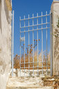 Iron gates halway opened leading into deserted garden greece Royalty Free Stock Images