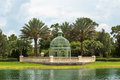 Iron gazebo and palm trees green dome shaped constructed of straight curved bars sits between two other green vegitation Stock Images