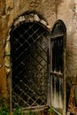 Iron grating behind the door in old stone wall Royalty Free Stock Photo
