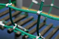 Iron joint point of ropes in children spider web with screw. Detail of cross green ropes in safety climbing outdoor equipment. Royalty Free Stock Photo