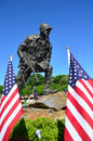 Iron mike us paratrooper american flags is the nickname of a foot tall statue of a u s who has apparently just landed on a big Stock Photo
