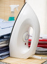 Iron an next to a pile of ironed clothes Royalty Free Stock Photography