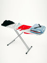Iron, red dress and stack of clothes on ironing board isolated o