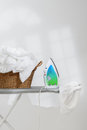 Ironing basket of freshly laundered washing and electric iron on board Stock Images