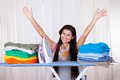 The ironing is finished happy woman throws her arms in air because she has and folded all of Stock Images