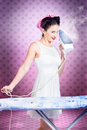 Ironing pinup housewife doing sixties housework gorgeous brunette working with steam iron inside retro polka dot home interior in Royalty Free Stock Photos