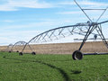 Irrigation in cultivated field and blue sky Stock Photography