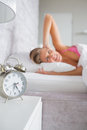 Irritated blonde covering her ears from the alarm clock noise at home in bedroom Royalty Free Stock Image